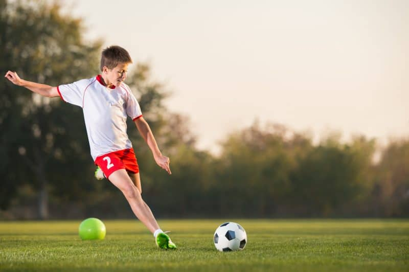 kid kicking a soccer ball on the field