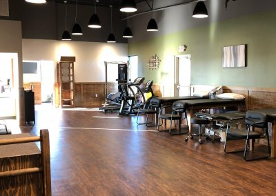 long physical therapy room with adjustment tables and workout equipment