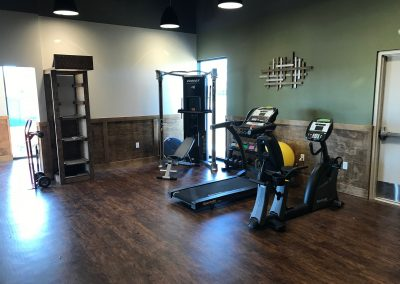 physical therapy room with stationary bike, treadmill and workout equipment